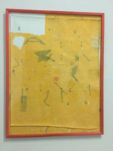 Photograph of a large yellow drawing under glass in an orange frame; the drawing continues onto the mat it is mounted on.