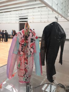 Photograph of articles of clothing on hangers; the clothes are made of plastic and billow with air from fans below.