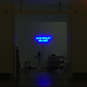 """A distant view through the darkness of a neon sign reading """"UltraViolet Archive"""""""