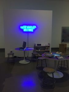 "A neon sign reads ""Ultraviolet Archive."" There are tables with books on them, with stools so people can sit and browse, as well as a computer."