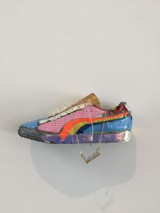 A sneaker decorated with strips of pink, orange, yellow, and blue tape, with silver duct tape around the base and a hanging charm. It's mounted to a white wall.