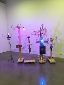 An installation in a museum consisting of several stacks of assorted found objects, united by wires and a purple glow.