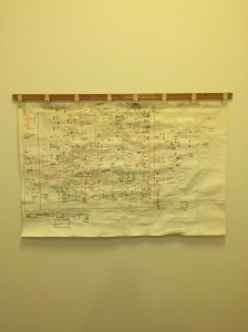 On a white wall hangs a large piece of paper with a large, complex diagram printed on it and annotated by hand.