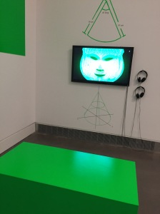 A green mask appears in a video on a monitor. The custom bench where visitors can sit and watch the video is a slick green block.