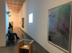 A view of a museum wall; a framed photograph is closest to the camera, the rectangle of a digital projector hovers in the middle, and at the far end hangs a painting whose dominant color is red.