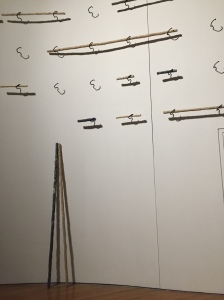 Rows of metal hooks hold sticks against a white wall, while a couple long sticks stand on the floor, leaning against the wall.